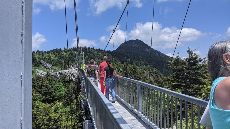 people crossing suspension bridge at grandfather mountain in north carolina